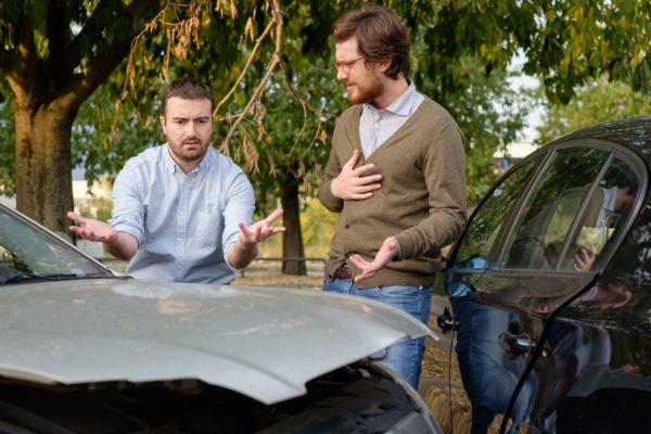 two men arguing about who is at fault for the car accident